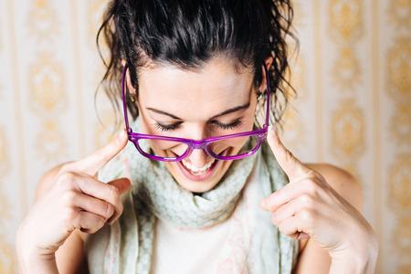Gelukkige vrouw draagt een bril, lacht en kijkt neer Eyewear vrouwelijke mode-concept