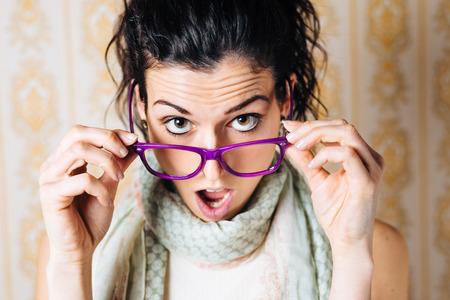 Überrascht Frau sucht über ihre Brille Schöne Mund offen Mädchen mit modernen Brillen Standard-Bild