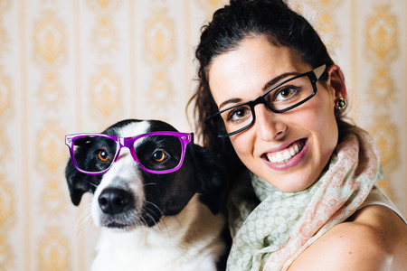 Funny woman and cute dog wearing glasses  Portrait of happy girl with her pet with eyewear  photo
