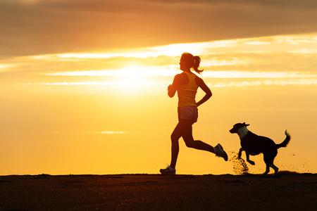 女性と無料ビーチの黄金日没フィットネス少女と彼女のペットは一緒にワークアウトで走っている犬