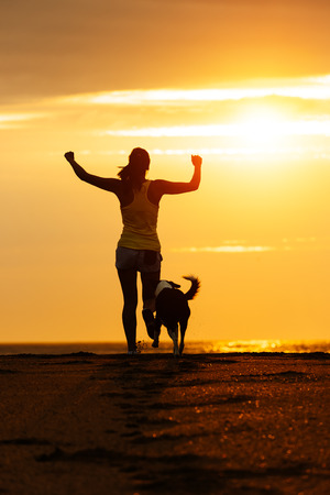 Woman and dog running free on beach towards the sun  Sport girl and her pet enjoying freedom and sport together