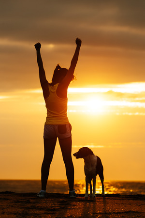 Successful woman and dog enjoying freedom on beautiful golden sunset  Fitness girl raising arms celebrating sport achievement with her pet  Stock Photo