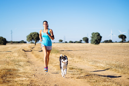 Woman and dog running in country side dirt track.  photo