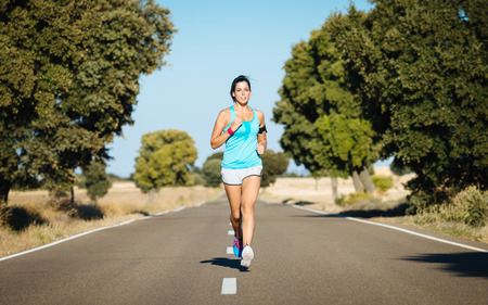 Sweaty woman running on rural road. Hispanic female athlete training and exercising hard for intense marathon.