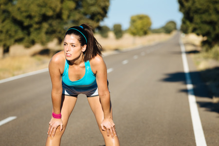 Tired female runner sweating and breathing after running hard in countryside road. Exhausted sweaty woman recovering after training on hot summer. Stock Photo