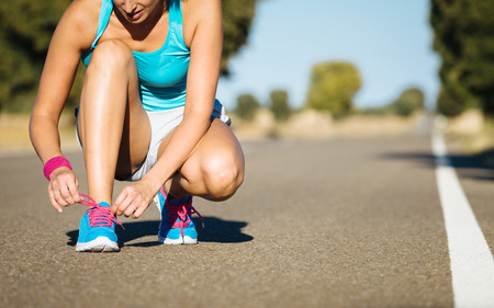 Female runner tying sportshoes laces for running on road. Athlete getting ready for training. Stock Photo