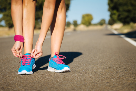 Female athlete tying sportshoes laces for running on road. Runner getting ready for training. Stock Photo