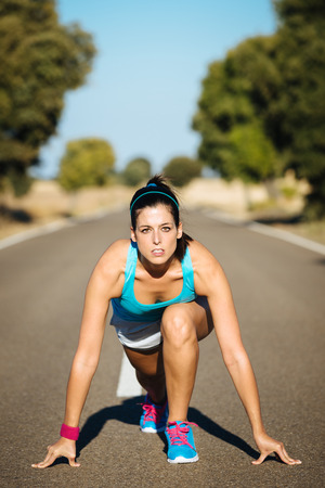 Athletic woman on running sprint challenge in countryside road. Fitness female runner in ready start line pose outdoors. photo