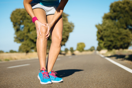 leg injury: Female runner knee injury and pain. Stock Photo