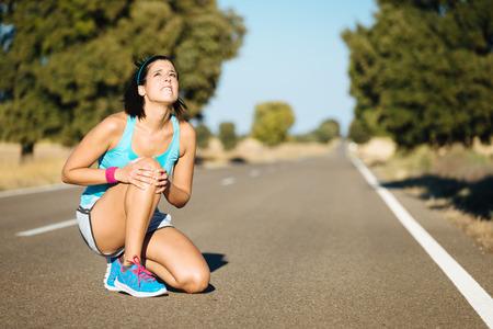 articulaciones: Mujer llorando por una lesi�n de rodilla dolorosa durante la carrera de formaci�n.