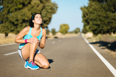 cramp: Woman crying for a painful knee injury during running training.