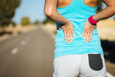 dolor muscular: Lesión en la espalda atleta atleta femenina y el dolor. Mujer que sufre de lumbago dolorosa o enfermedad renal mientras se ejecuta en el camino rural.