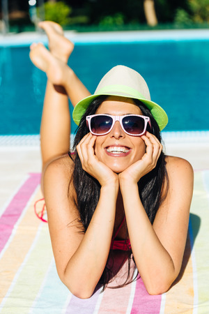 Woman sunbathing on summer vacation at swimming pool. Relaxed joyful girl portrait. photo