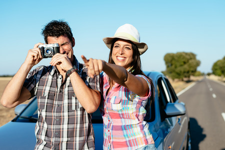 relaxed man: Happy couple on car roadtrip tourism  Man and woman on road travel vacation taking photos with retro camera  Stock Photo