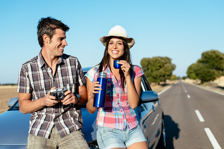 roadtrip: Happy couple on car roadtrip tourism  Man and woman on road travel vacation taking a break for drinking and taking photos