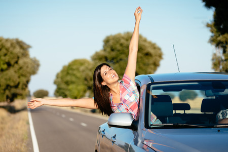 outstretching: Blissful woman on car travel raising arms  Happy brunette girl enjoying freedom on roadtrip vacation  Stock Photo