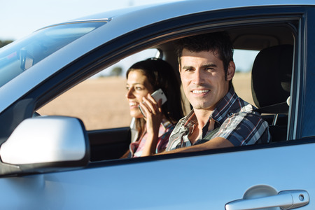 roadtrip: Couple on summer car roadtrip  Casual man driving and woman talking on cellphone  Stock Photo