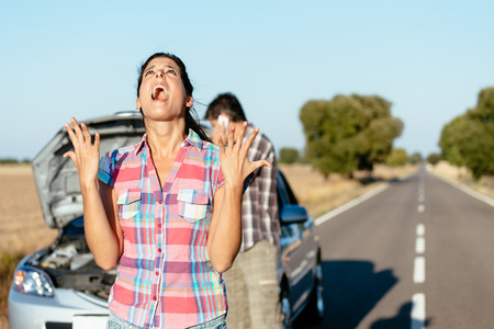 Desperate woman praying desperately because of car problems. Despair couple waiting for help after engine breakdown.