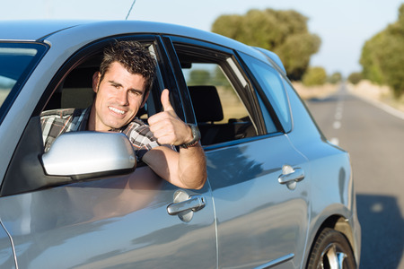 Successful man driving car and doing thumbs up. Cheerful male driver approving. photo