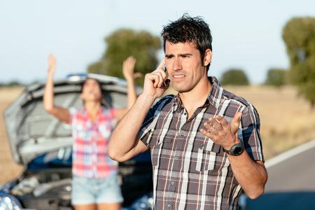 車保険サービスと携帯電話上と主張する男。エンジン故障のため道路の旅行の問題のカップルを混乱させます。