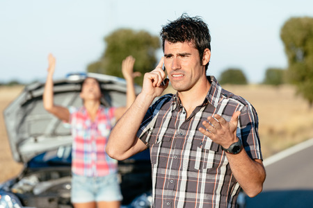 Man arguing on the cellphone with car insurance service. Upset couple in road trip problems because of breakdown engine. Stok Fotoğraf
