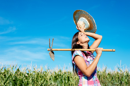 Tired female farmer working with hoe in corn field. Countryside sweaty woman with work tool wearing straw hat and chekered shirt.