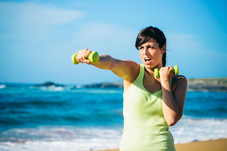 Fitness woman punching hard for working out with dumbbells on beach. Summer intense workout. photo