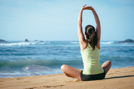 Fitness girl doing relaxing and breathing towards the sea on beach. Woman stretching arms. Imagens