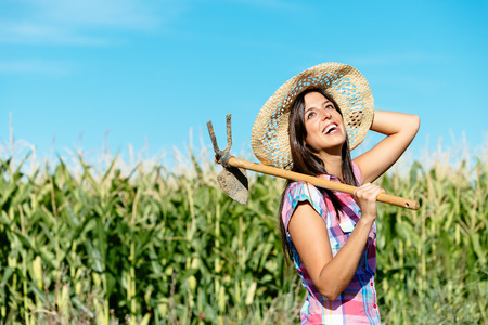 hoe: Successful female farmer carrying hoe in corn field and smiling. Countryside woman with work tool wearing straw hat and chekered shirt.