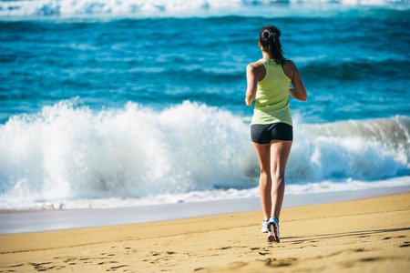 Fitness woman running towards the sea on beach. back view runner. photo