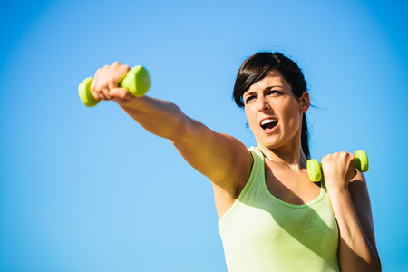 Fitness woman punching for intense working out with dumbbells on clear sky background. Stock Photo