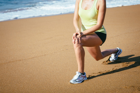 Fitness woman stretching legs on the beach for warming up before running. photo