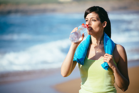 Exhausted fitness woman drinking water after working out on beach. Sporty girl taking a training break. photo