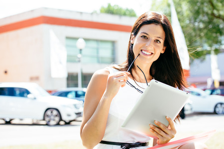 Successful female car sales consultant in business trade fair showing blank digital tablet screen and approving with thumbs up  Vehicle offer and information concept  photo