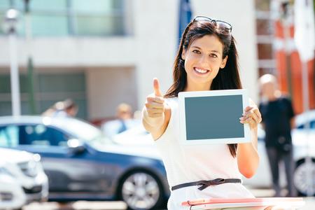 Weibliche Pkw-Verkaufsberater im Geschäft Messe zeigt leere digitale Tablet-Bildschirm und Genehmigung mit Daumen nach oben Fahrzeugangebot und Informationskonzept Standard-Bild - 26712980