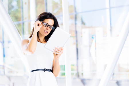 touchpad: Modern woman reading digital business info in tablet  Young businesswoman using touchpad