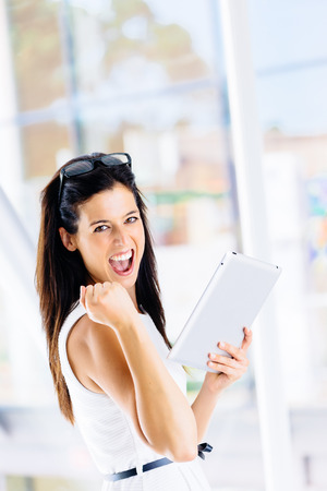 Successful woman celebrating achievement with digital tablet indoor  photo