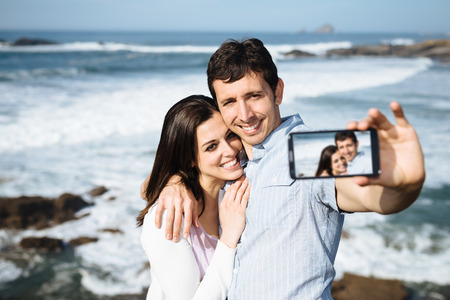 Young couple on honeymoon travel in Asturias coast, Spain, taking selfie portrait photo with smartphone camera