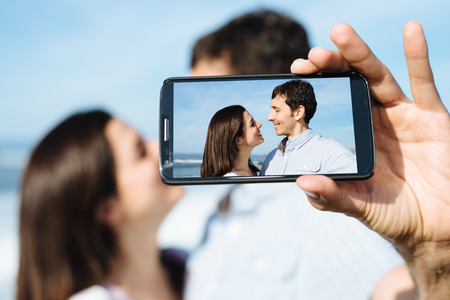 romantic picture: Young couple on honeymoon travel taking selfie portrait photo with smartphone camera  Stock Photo