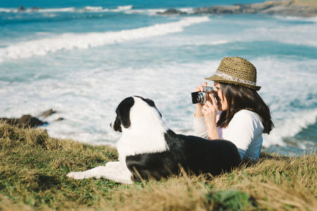 Happy hipster woman taking photo to her dog on vacation travel  photo