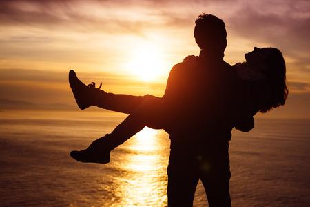 silhouettes lovers: El par juguet�n joven en el amor al atardecer se divierten hacia la escena de los amantes rom�nticos del mar