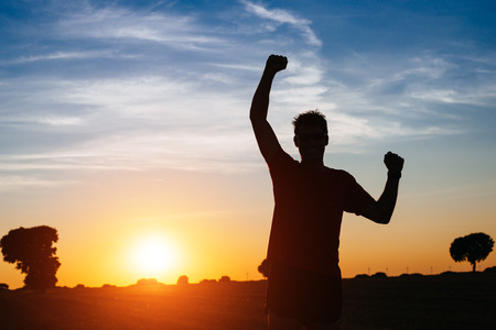 成功した男の腕を行使し、ワークアウト後の成功とスポーツの目標を祝うと日没のオスの運動選手で夏を実行しているクロスカントリー後に腕を上 写真素材