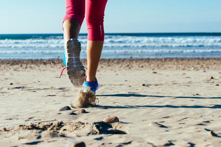 feet in sand: Woman running fast on beach  Female runner legs and sport footwear detail  Stock Photo
