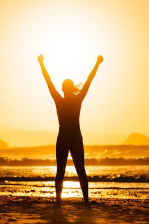 Fitness vrouw vieren sport succes op mooie zomerse zonsondergang of 's morgens op het strand Succesvolle vrouwelijke runner silhouet verhogen van armen naar de zon