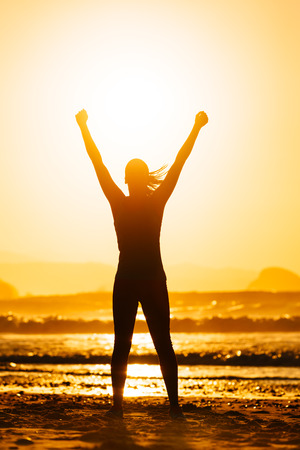 achiever: Fitness woman celebrating sport success on beautiful summer sunset or morning on the beach   Successful female runner silhouette raising arms to the sun
