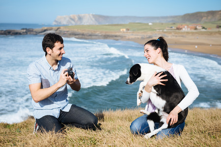 Young couple and dog on travel in Asturias coast, Spain  Man taking photo to her girlfriend with retro camera  photo