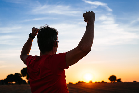 Successful man raising arms after cross country running on summer at sunset  Male athlete with arms up celebrating success and freedom after sport exercising and working out  Stock Photo