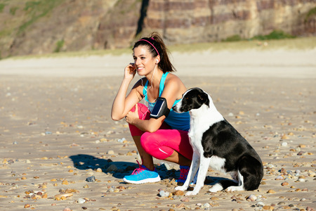 female athlete: Relaxed fitness woman with dog listening music with sport arm band and earphones at the beach  Sporty girl taking a breath before running
