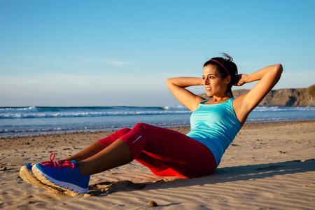 Fitness Frau macht Sit-ups, die auf Strand Sportliche Mädchen Training im Freien im Sommer Standard-Bild