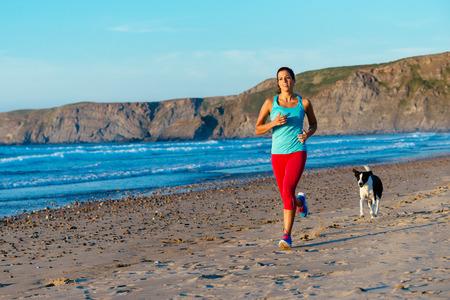 Fitness Frau und Hund auf Lauftraining am Strand Sportlich Läuferin Training auf Sommer Sonnenuntergang